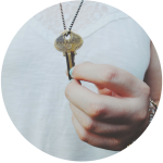 woman holding key necklace stamped fearless